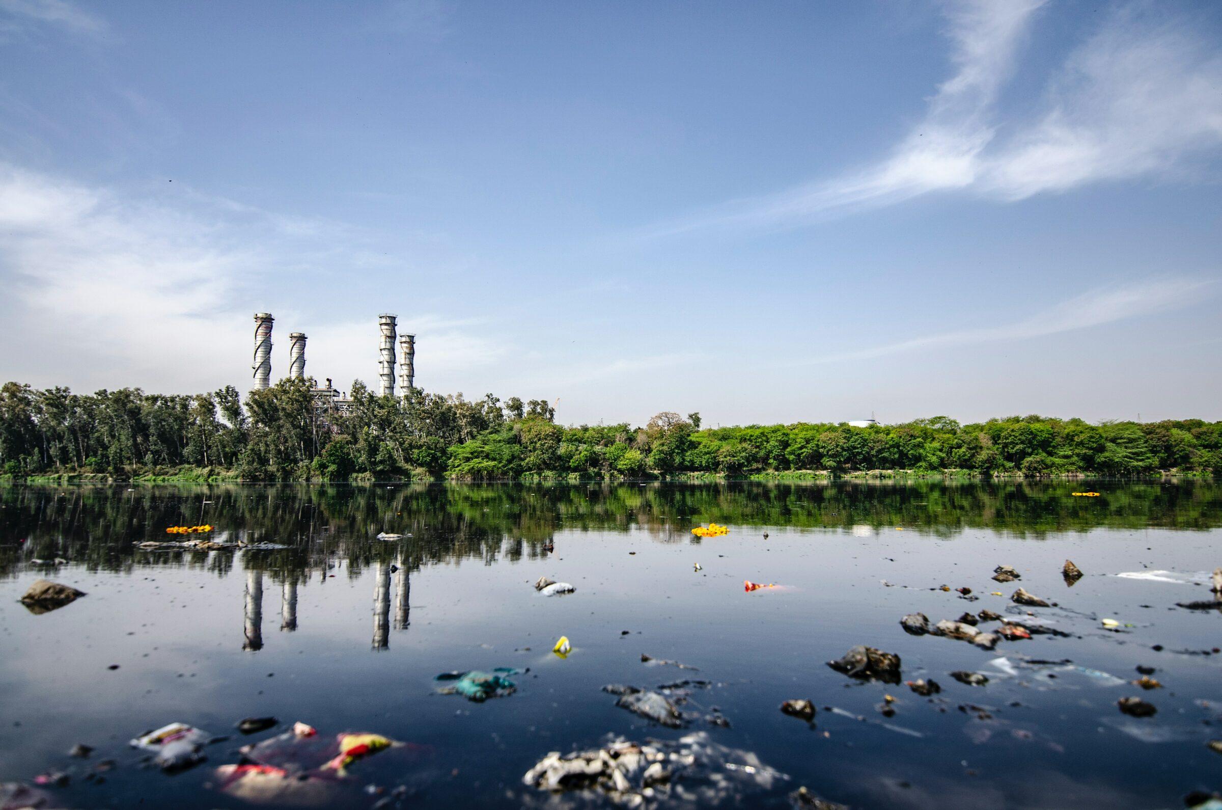 Mit Plastikmüll verschmutztes Gewässer. Im Hintergrund sind Schornsteine einer Fabrik zu sehen.